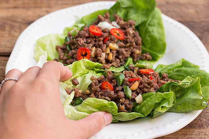 A close up horizontal image of a hand from the left of the frame picking up a ground beef in lettuce wrap from a white plate set on a wooden table.