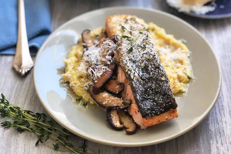A close up horizontal image of roasted salmon with shiitake mushrooms and parmesan grits on a beige plate set on a wooden table.