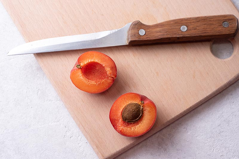 A close up horizontal image of an apricot sliced in half on a chopping board with a knife.