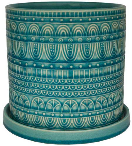 A close up square image of a blue decorative ceramic pot with a saucer at the bottom isolated on a white background.