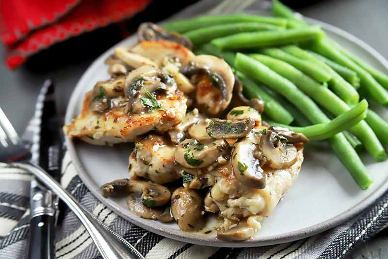 A close up horizontal image of a plate of chicken and mushrooms with green beans.
