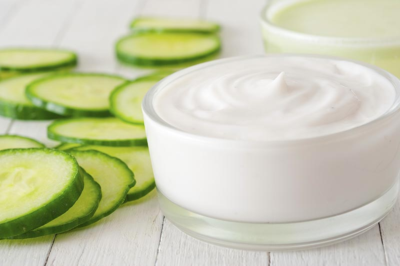A close up horizontal image of slices of cucumber set on a white wooden surface with a homemade face cream to the right of the frame.