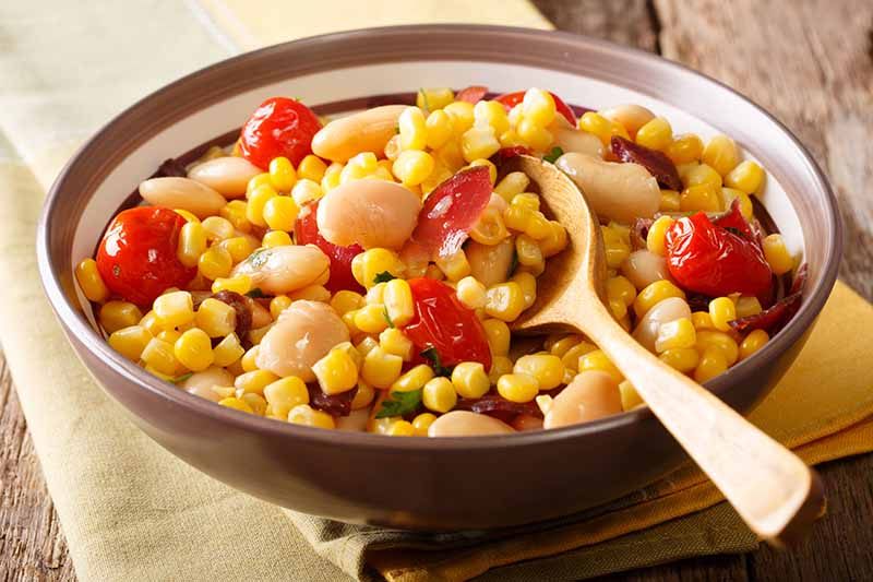 A close up horizontal image of a dish of freshly prepared succotash set on a wooden table.