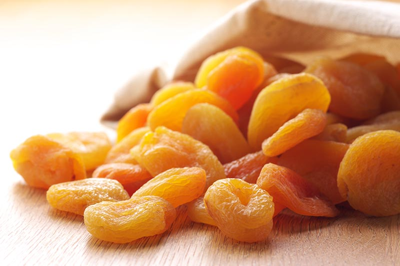 A close up horizontal image of dried apricots spilling out of a cloth bag on to a wooden surface.