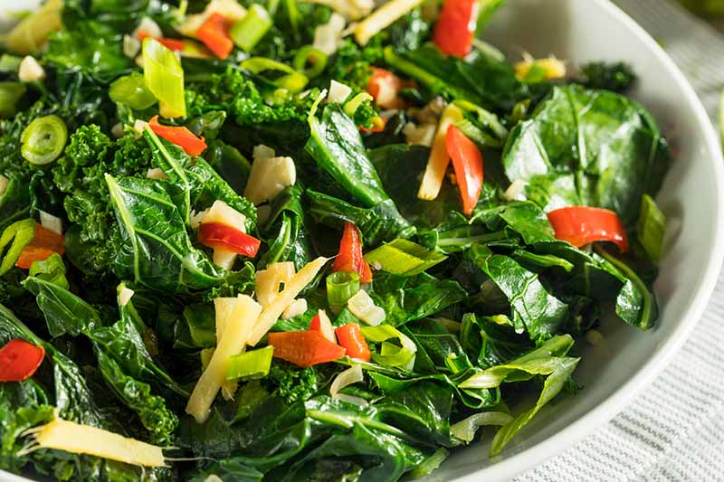 A close up horizontal image of a dish of cooked kohlrabi greens with pepper and ginger.