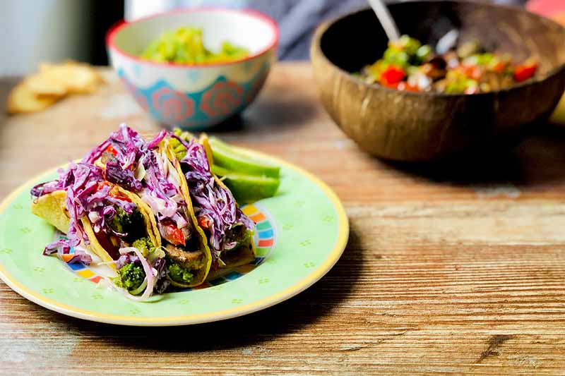 A close up horizontal image of a plate of garlic and ginger tacos served with slaw set on a wooden surface, with a wooden bowl in the background in soft focus.