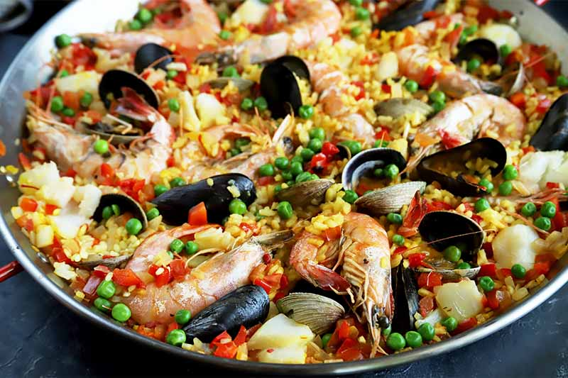 A close up horizontal image of a pan with homemade paella.