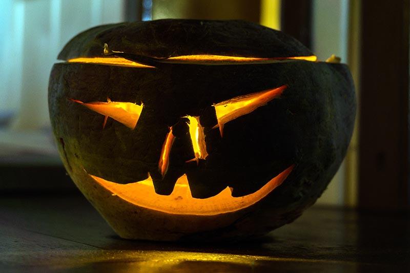 A close up horizontal image of a turnip carved into a Jack-o-Lantern with a light inside.