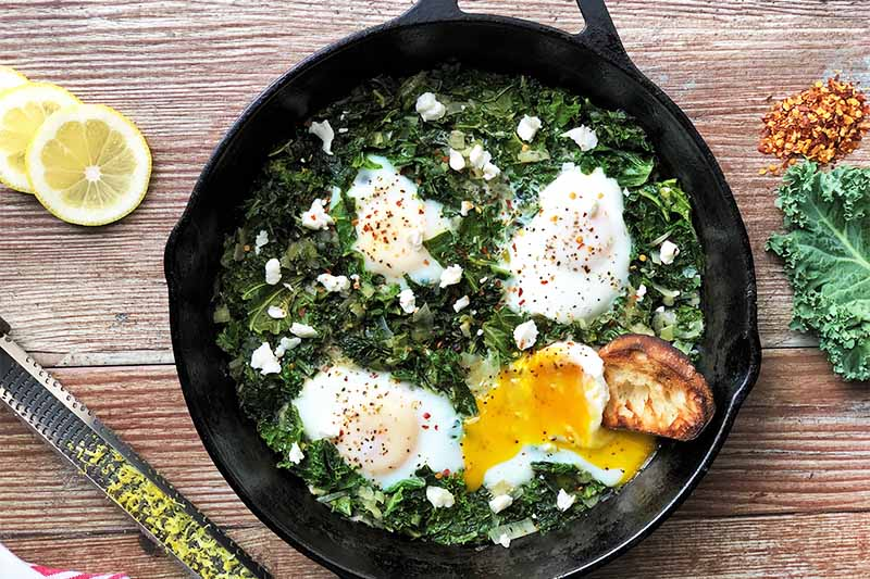 A close up horizontal image of a skillet with freshly prepared kale and eggs set on a wooden surface.