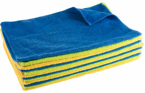 A close up horizontal image of a pile of microfiber cloths isolated on a white background.