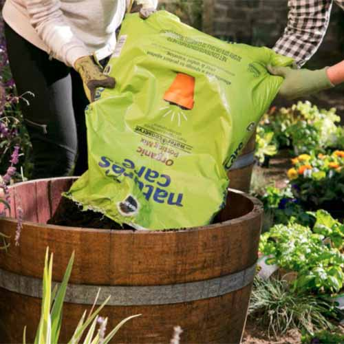 A close up square image of two gardeners emptying a bag of Nature's Care Potting Mix into a large whiskey planter container.