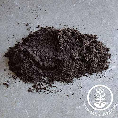 A close up square image of a pile of soil inoculant set on a dark gray surface. To the bottom right of the frame is a white circular logo with text.