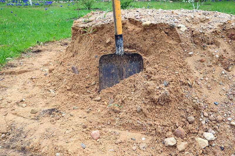 A close up horizontal image of a shovel set in a pile of landscape sand.