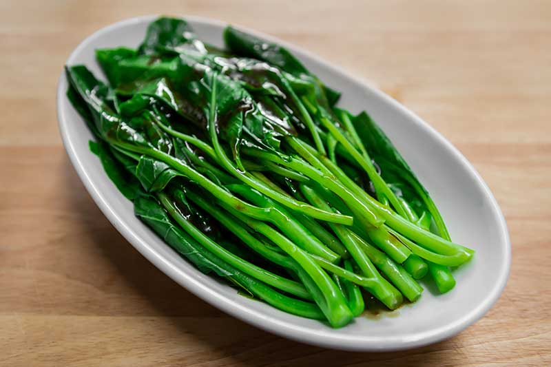 A close up horizontal image of stir fried Chinese broccoli in a white plate set on a wooden surface.