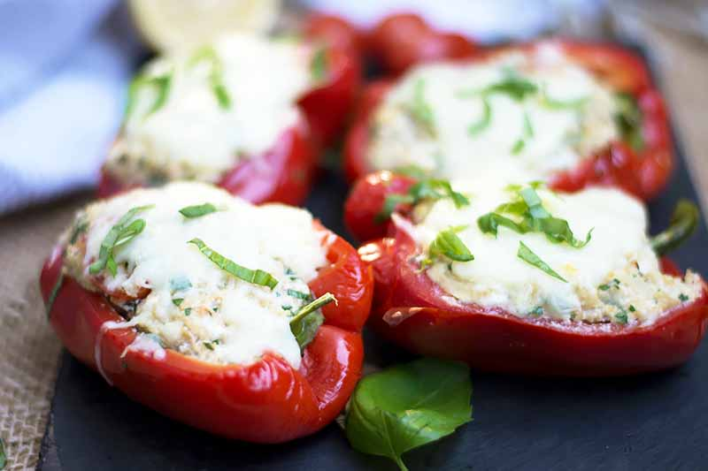 A close up horizontal image of homemade stuffed bell peppers set on a gray slate.