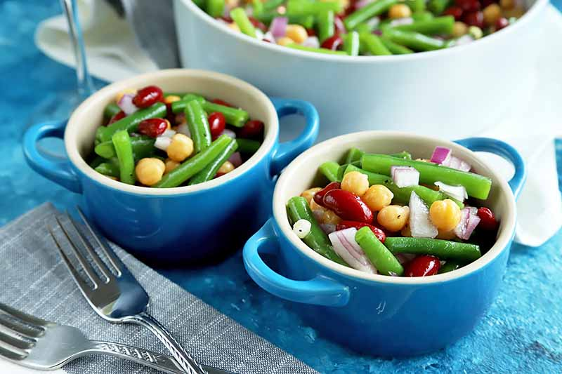 A close up horizontal image of two bowls of freshly prepared three bean salad set on a blue surface.