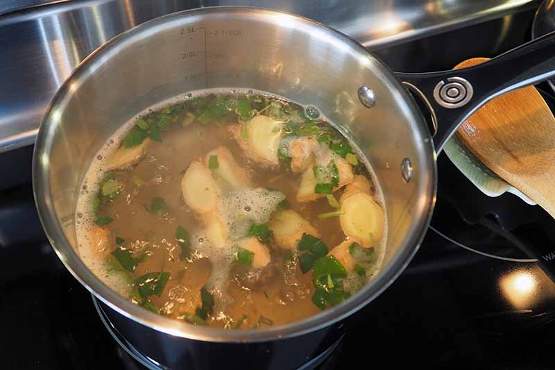 A close up horizontal image of a pan with ingredients to make soothing herbal tea on a hot stove.