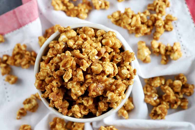 A close up horizontal image of a bowl of caramel popped corn set on a fabric surface with popcorn scattered around.