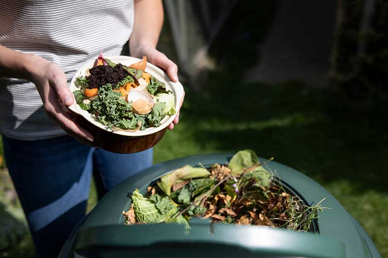 A close up horizontal image of a gardener putting a bowl full of food scraps into a plastic compost bin.