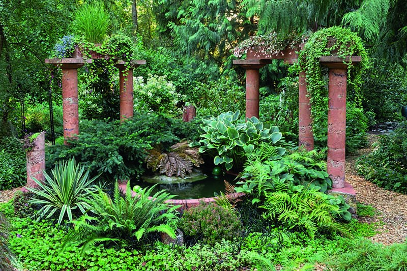 A close up horizontal image of a foliage garden around a water features with pillars in the background.