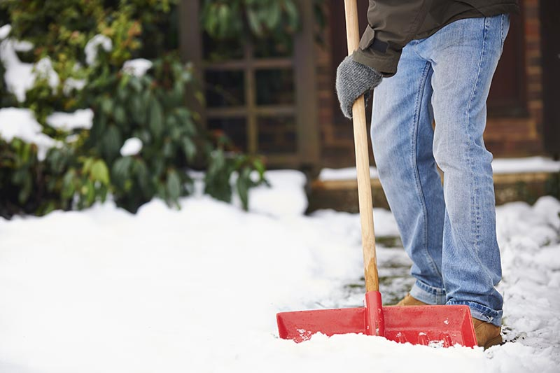 A close up horizontal image of a homeowner using a wooden-handled shovel to move snow from a pathway.