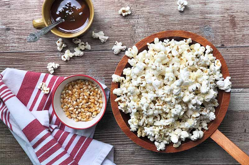 A close up horizontal image of a bowl of popped corn set on a wooden surface with a small bowl of kernels on the left.
