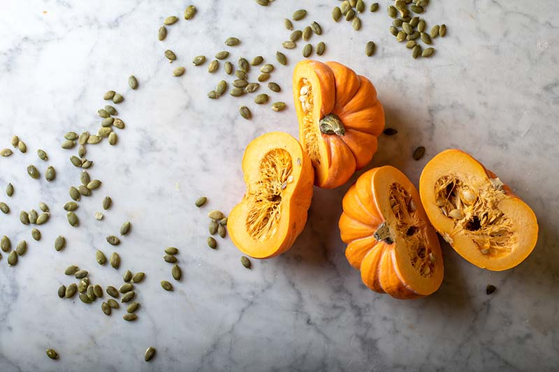 A close up horizontal image of two small pumpkins cut in half set on a marble surface with seeds scattered around.