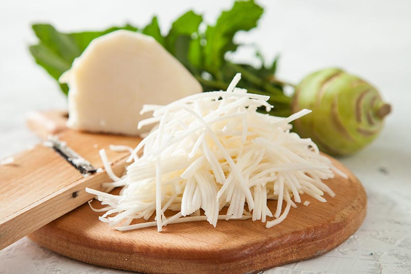 A close up horizontal image of grated kohlrabi on a wooden chopping board with a whole one in the background.