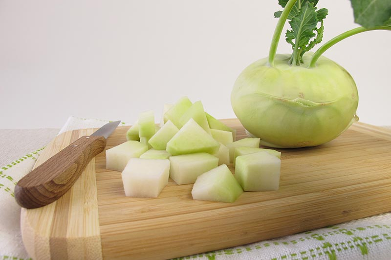 A close up horizontal image of a whole and chopped kohlrabi bulb on a wooden chopping board pictured on a white background.