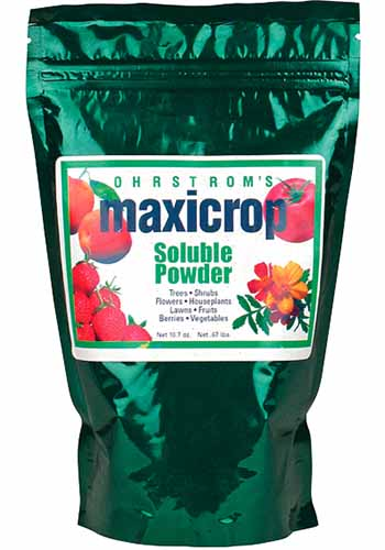 A close up vertical image of the packaging of Maxicrop Soluble Powder isolated on a white background.