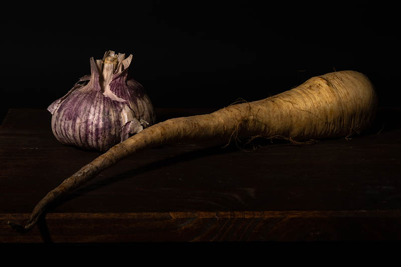 A close up horizontal image of a garlic bulb and a parsnip set on a wooden surface in moody dark lighting.