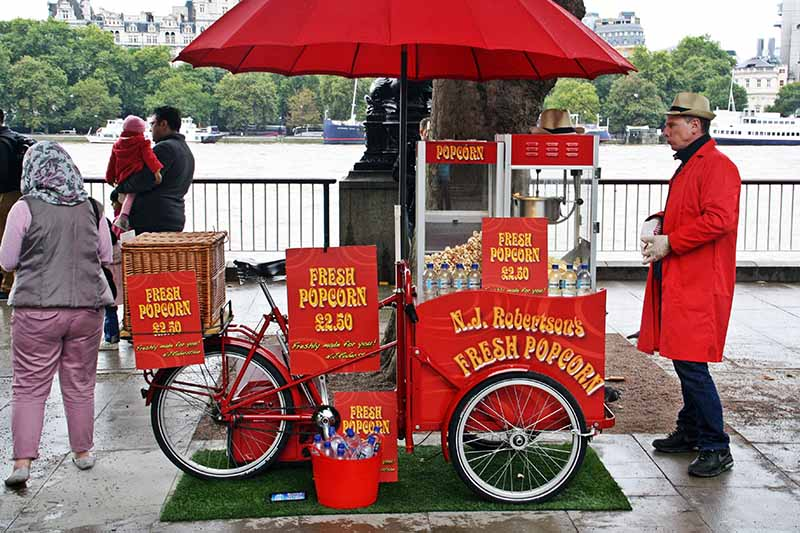 A horizontal image of an old-fashioned popcorn cart on a bridge in London.