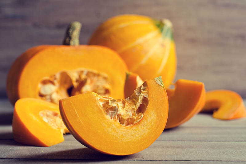 A close up horizontal image of pumpkins sliced and whole set on a wooden surface.