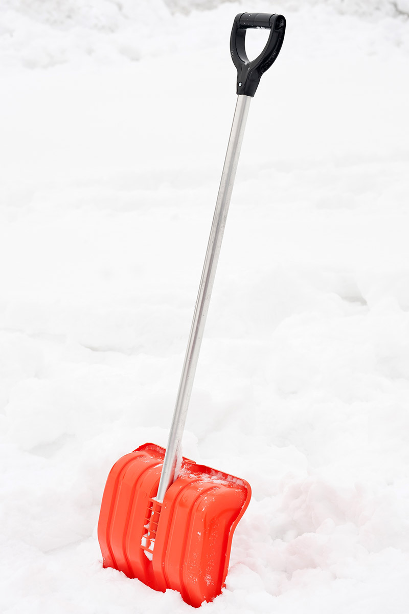 A close up vertical image of a red shovel with a metal handle in the snow.