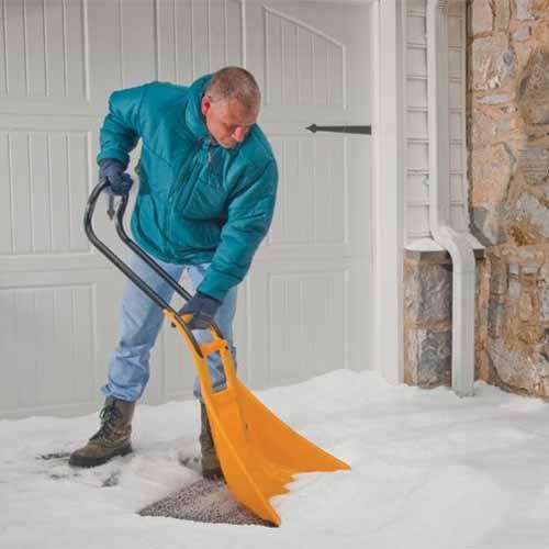 A close up square image of a man shoveling snow with a True Temper SnoBoss.