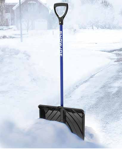 A close up vertical image of a snow shovel on a driveway filled with the white stuff.