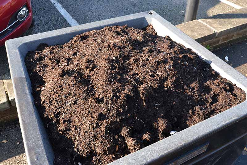 A close up horizontal image of a square plastic planter filled with soil ready for planting vegetables.