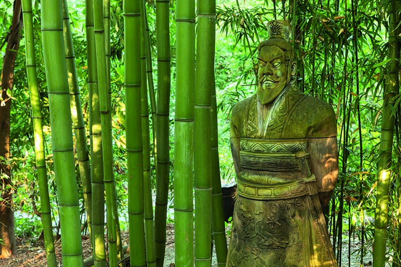 A close up horizontal image of a stone statue in a bamboo garden.