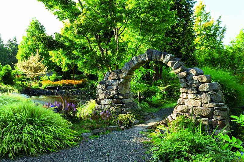 A close up horizontal image of a circular stone gateway over a path through a garden.