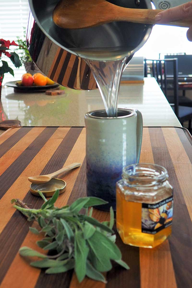 A close up vertical image of a herbal tea being poured from a saucepan into a ceramic mug on a wooden surface.