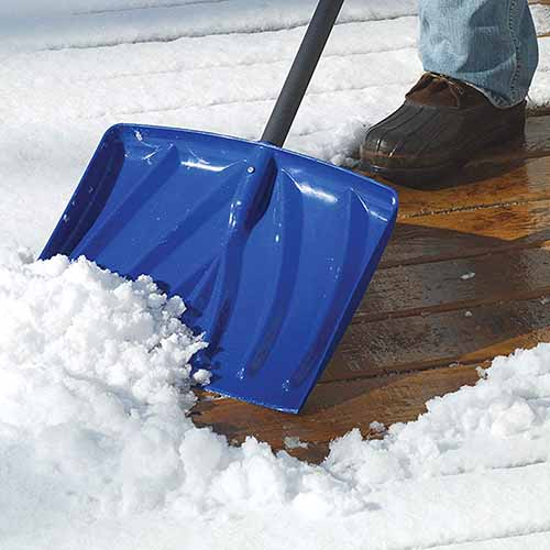 A close up square image of a person using a blue shovel to move snow from a wooden deck.