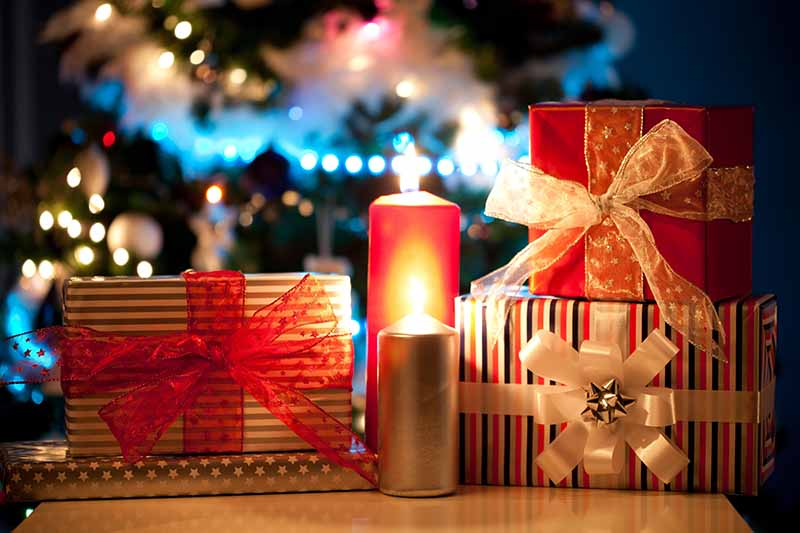 A close up horizontal image of beautifully wrapped gifts set on a wooden surface with candles and fairy lights in the background.