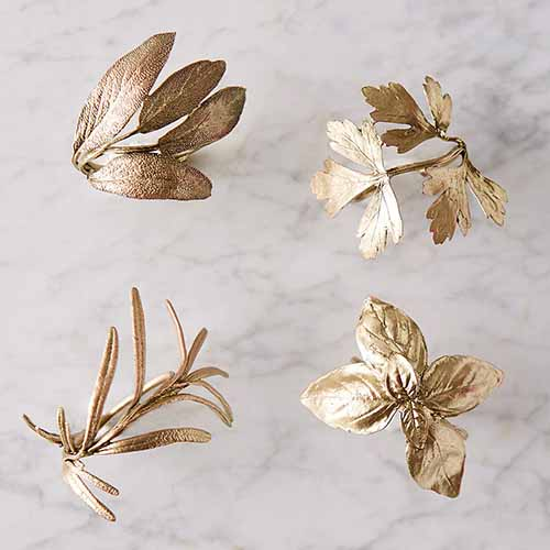A close up square image of four napkin rings in the shape of herbs set on a marble surface.