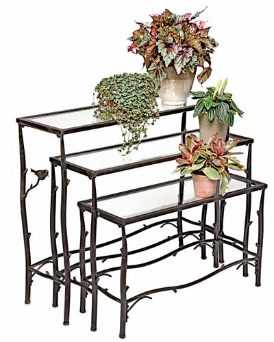 A close up vertical image of three nested tables each with potted plants set on top of them.