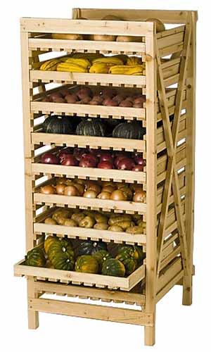 A close up vertical image of a wooden produce storage rack filled with a variety of fresh vegetables isolated on a white background.